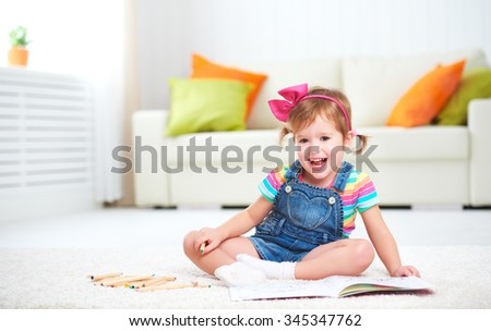 happy child girl drawing with colored pencils lying on the floor in the nursery - stock photo
