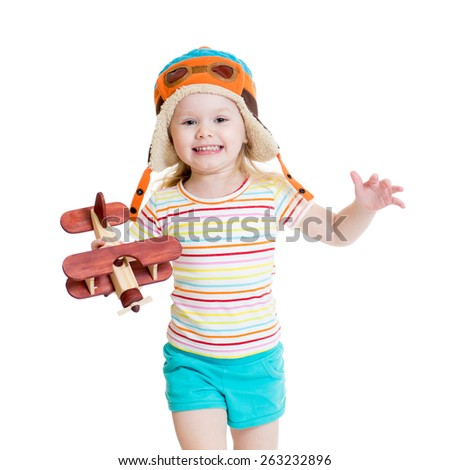 happy child girl dressed pilot and playing with wooden airplane toy - stock photo