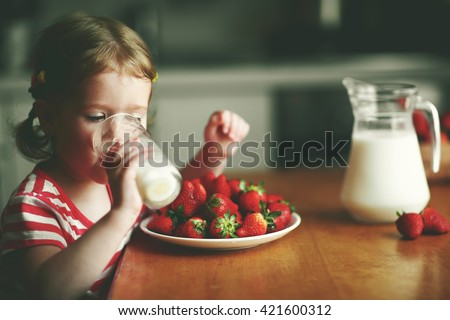 happy child girl drinks milk and eats strawberries in the summer home kitchen - stock photo