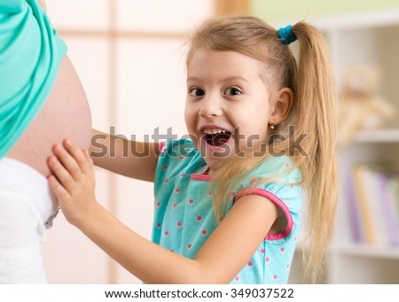 Happy child girl embraces her mother pregnant tummy - stock photo