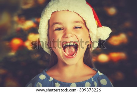 happy child girl in a Christmas hat waiting for a miracle - stock photo