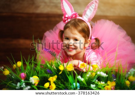 Happy child girl in a costume Easter bunny rabbit with  eggs, grass and flowers - stock photo