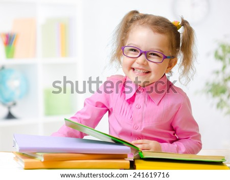 Happy child girl in glasses reading books in room - stock photo