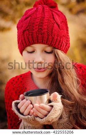 happy child girl in warm red knitted hat and scarf on cozy autumn walk drinking hot tea from thermos. Seasonal outdoor activities - stock photo