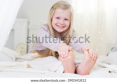 Happy child girl is smiling in the bed barefoot - stock photo