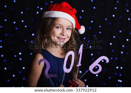 Happy child girl is wearing red santa hat holding paper digits 2016 in hands in a studio over background scene with blue lights, new year and christmas - stock photo