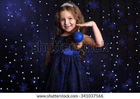 Happy child girl is with blue Christmas tree toy in hands over background scene with lights, New years - stock photo
