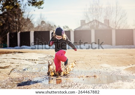 happy child girl jumping in spring puddle with big splash - stock photo