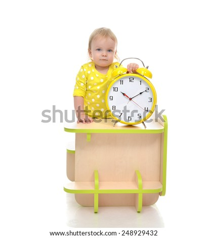 Happy child girl kid standing near little table with big yellow alarm clock isolated on a white background - stock photo