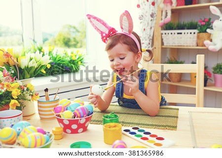 Happy child girl paints eggs for Easter at home - stock photo