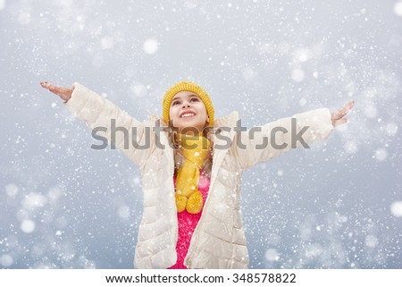 happy child girl plaing on a snowy winter walk