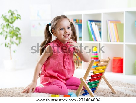 happy child girl playing with abacus toy in nursery - stock photo