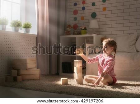 Happy child girl playing with blocks and having fun. - stock photo
