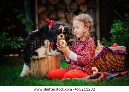 happy child girl with her dog harvesting apples in autumn garden, kid training her dog and feed him