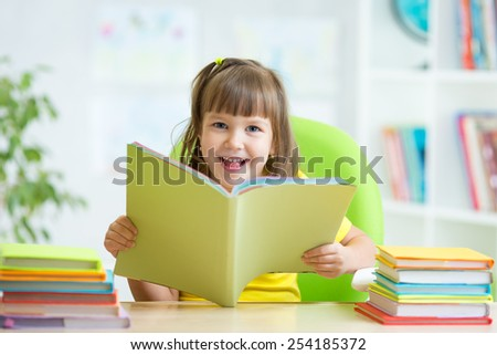 Happy child girl with opened book at nursery - stock photo