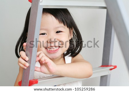 Happy child grinning while holding onto a metal ladder - stock photo
