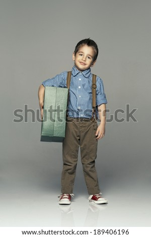 happy child have a present on grey background  - stock photo