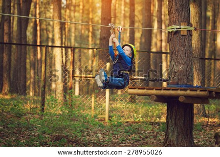 Happy child, healthy  boy enjoying activity in a climbing adventure park on a summer day.Flies on a bungee - stock photo