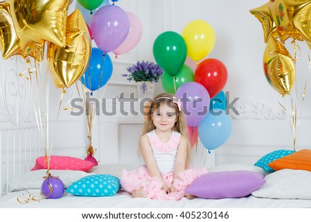 Happy child holding bunch of air balloons. portrait of beautiful little girl smiling and holding balloons in studio with many balloons around. Little girl with multicolored air balloons - stock photo