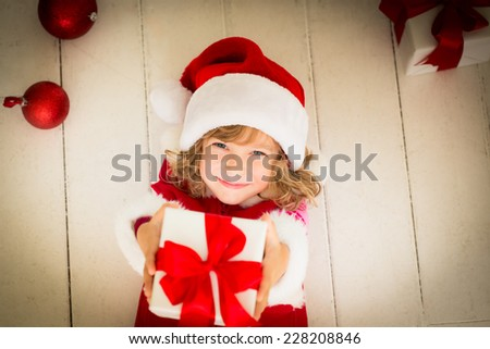 Happy child holding Christmas gift. Kid dressed in Santa Claus hat lying on wooden floor. Funny baby at home. Xmas holiday concept - stock photo