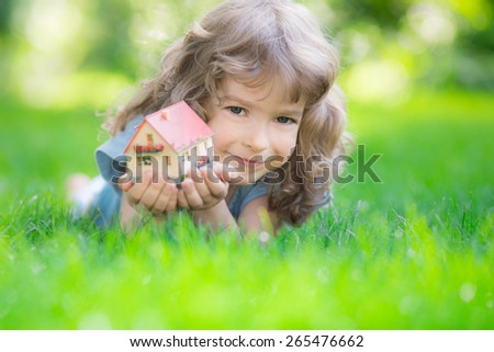 Happy child holding model house in hands. Kid lying on green grass in spring park. New home concept - stock photo