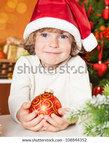 Happy child holding red ball against Christmas decorations