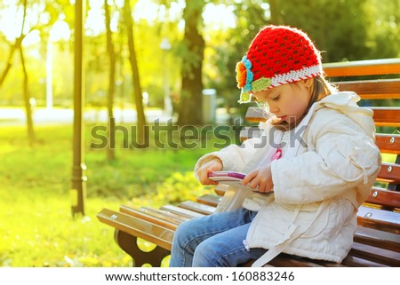 Happy child holding tablet PC in autumn park - stock photo