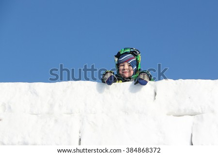 Happy child in a color jacket with a hood at wall top from snow blocks