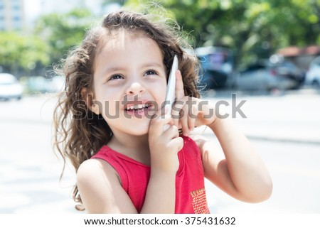 Happy child in a red shirt talking at phone