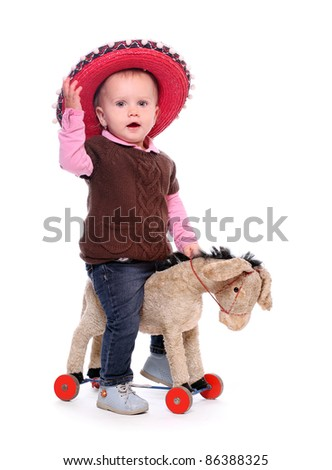 Happy child in big hat on a rocking donkey.
