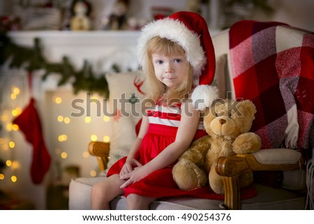 Happy child in Santa hat sitting on chair