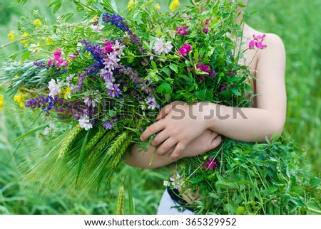 Happy Child in Summer. Kid with big bouquet of Flowers in his hands in the Garden. Happy Children. Healthy Kids. Spring Time. Vacation in the Countryside. - stock photo