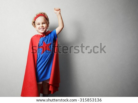 Happy child in superhero suit against gray wall. - stock photo