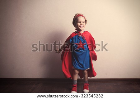 Happy child in superhero suit against gray wall. Tinted photo - stock photo