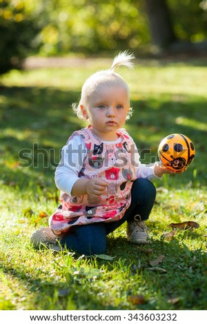 Happy child is outside in the park. She is looking at camera and playing with her ball.  - stock photo