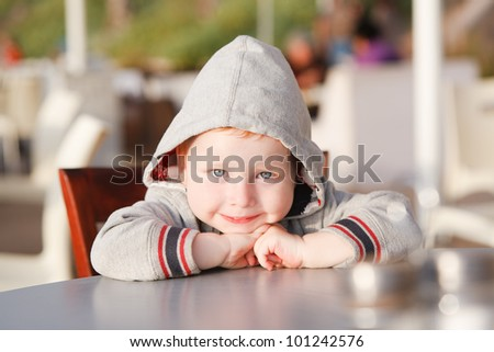 Happy child is sitting at a table and smiling - stock photo