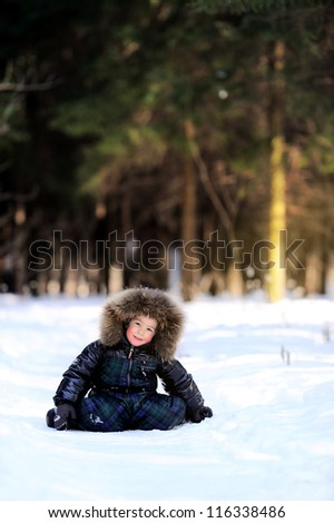 Happy child is sitting in the winter forest. Sunny day and a lot of snow.