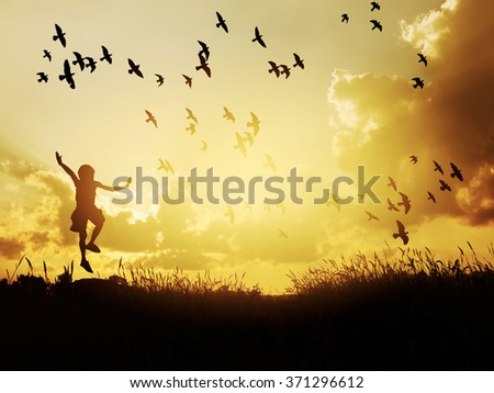 Happy child jumping with birds in sunset sky. - stock photo