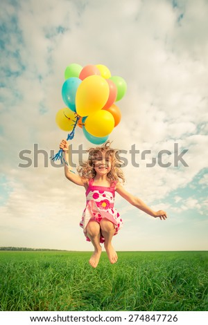 Happy child jumping with colorful toy balloons outdoors. Smiling kid having fun in green spring field against blue sky background. Freedom concept - stock photo