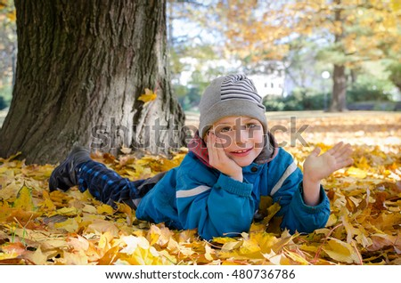 Happy child laying in autumn leaves under a maple tree in park in fall.