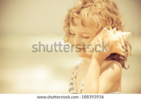 Happy child listen to seashell at the beach. Summer vacations concept - stock photo
