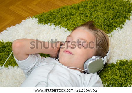 Happy child listening to music through headphones while lying on a carpet.
