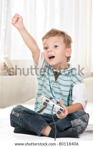 Happy child - little boy playing a video game - stock photo