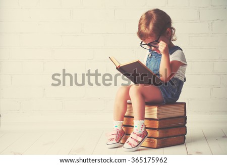 happy child little girl with glasses reading a books - stock photo
