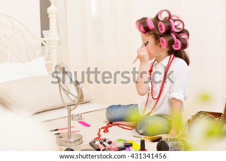 Happy child. Little pretty girl makes a make-up on a bed in the bedroom . Girl laughing with curlers on her head , and brushes for makeup in the hands - stock photo