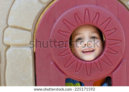 Happy child looking through a round window of a playhouse in a playground. - stock photo
