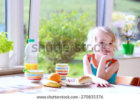 Happy child of preschool age, blonde curly toddler girl, enjoying healthy breakfast eating sandwich and fruits and drinking orange juice sitting at bright sunny kitchen next to big garden view window - stock photo