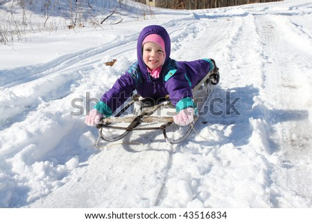 Happy child on a sled - stock photo