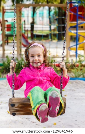 Happy child on a swing - stock photo