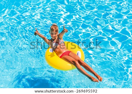 Happy child on inflatable ring in swimming pool. - stock photo